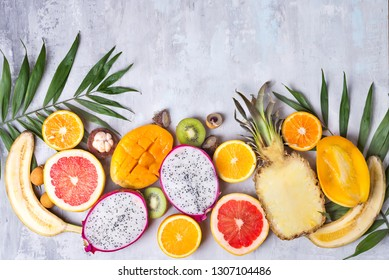 Tropical fruits assortment on a stone light background with palm leaf. Top view.