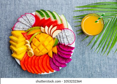 Tropical fruits assortment on a white plate with fresh juice, textile grey background. Top view. Copy space.