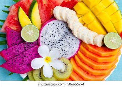Tropical fruits assortment on a white plate with palm leaf. Blue background. Top view. Copy space.