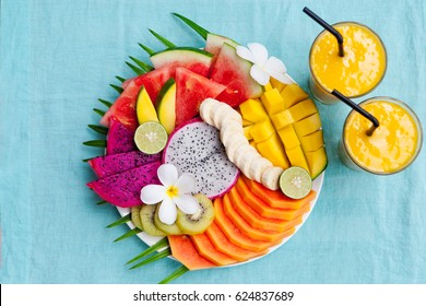 Tropical fruits assortment on a white plate with mango smoothie, textile blue background. Top view.