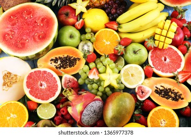 Tropical fruits background, many colorful ripe tropical fruits on wooden table