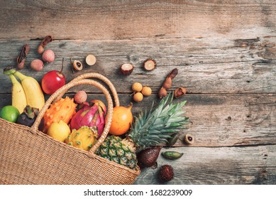 Tropical fruits in a basket on wooden background. Top view. Copy space. Tropical fruits flat lay. Zero waste, plastic free concept. Travel and holiday concept. Vegan, vegetarian healthy diet. Banner.
