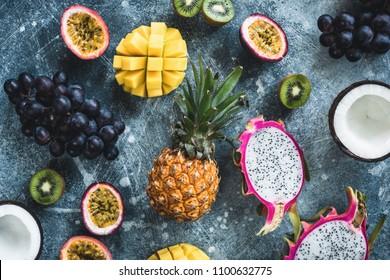 Tropical fruits, exotic fruits on concrete background. Fruit flat lay. Dragonfruit, passionfruit, coconut, mango, kiwi and grapes. Fresh raw fruit background