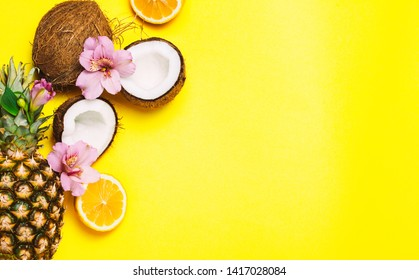 Tropical fruits and flowers on yellow background. Pineapple, cocnut, orange. Top view, flat lay. Copyspace for text.