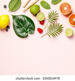 Tropical fruits and leaves on pink pastel background. Top view, flat lay, space for text