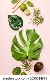 Tropical fruits and leaves on pink pastel background