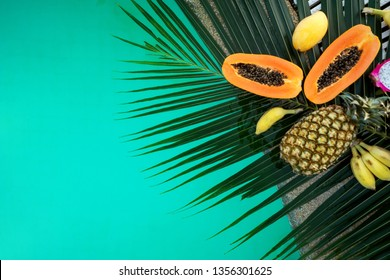 tropical fruits lie on palm leaves near the pool