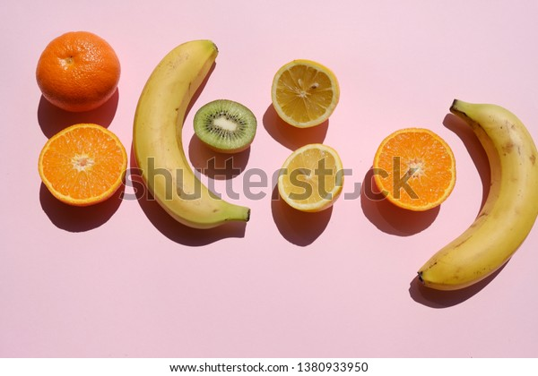 Tropical fruits on a pink background in sun light, top view, summer vibe