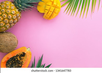 Tropical fruits on pink color background. Pineapple, papaya, coconut and mango flat lay. Exotic summer food concept with copy space