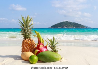 Tropical fruits on the sandy beach against the turquoise sea. Similan Islands, Thailand