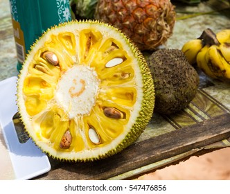 Tropical fruits on a table. In front is the jackfruit (which is the largest tree-bourn fruit) with its bright yellow pulp and large seeds. Behind is bananas and ananas.