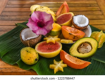 Tropical fruits - papaya, avocado, carom, coconut, mangoes, bananas on a palm leaf