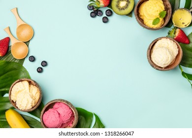 Tropical fruits and plants with variety of ice cream in coconut shells on blue background, flat lay