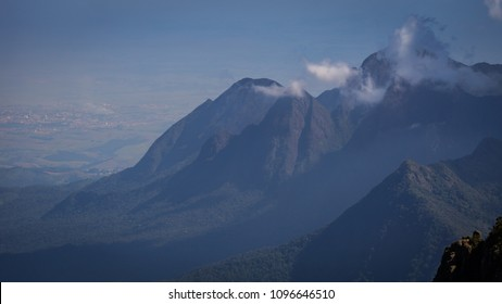Tropical green forest landscape on a high mountain with horizon to background and clouds on top of mountain in Brazil.
