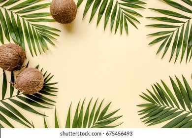 Tropical green leaves palm fronds and coconuts isolated on yellow background. the apartment lay, top view
