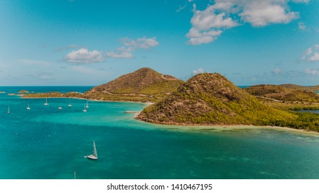 Tropical green mountains surrounded by turquoise water, exotic bay for sailboats in Antigua, Jolly Harbour for sailors, sailing