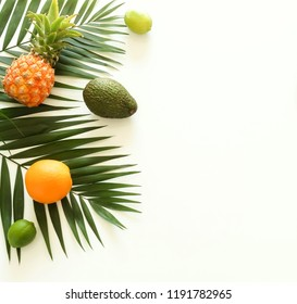 tropical green palm leaves branches and fruits pineapples top view on a white background. food concept.copy space