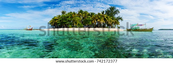 Tropical Guyam Island with traditional fishing boats, Siargao, Philippines