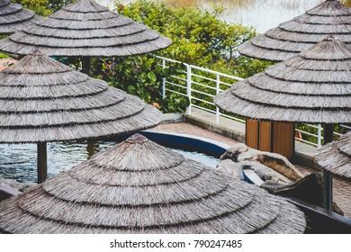Tropical hay umbrellas by a pool