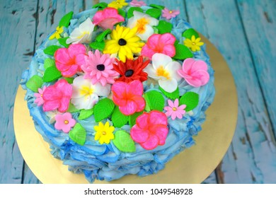 Tropical inspired cake with butter cream and different type of flower made of fondant