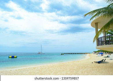 Tropical island beach scene/setting. Relaxing Caribbean summer vacation. People relaxing at Doctors Cave Beach Bathing Club on the Hip Strip in Montego Bay, Jamaica.
