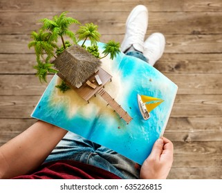 Tropical island with bungalow and pier on a page of opened magazine in hands. Unusual travel 3d illustration. Summer vacation concept
