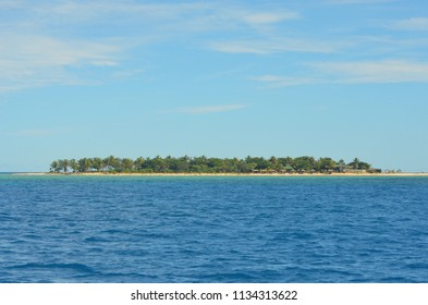 A tropical island glimmers in the sunshine. It is covered with trees, and the sand is golden. The sky is blue with soft clouds, and the ocean blue.