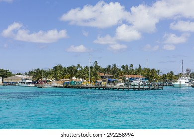 Tropical island harbor with boats and houses with turquoise water and blue sky