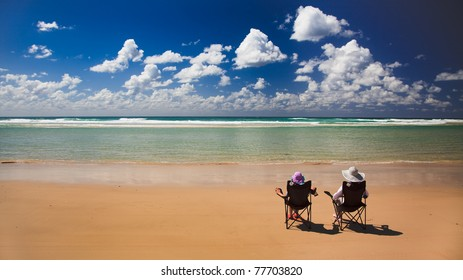 tropical island lonely sandy beach with clear warm water blue sky and two women sitting in chairs under sun