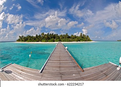 Tropical island with long jetty and blue sky with white clouds.