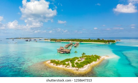 Tropical island with luxury resorts in Maldives from aerial view