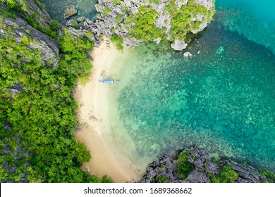 Tropical island on the atoll and turquoise lagoon. Rocky island with white sandy beach, aerial view. Caramoan Islands, Philippines.