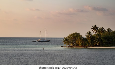 Tropical island and sailing yacht at sunset