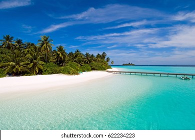 Tropical island with white beach, turquoise lagoon and blue sky.