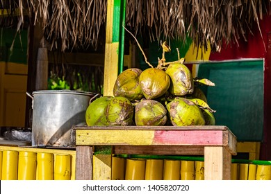 Tropical jelly coconut fruits on table at outdoor vendor shop painted in rasta colors with thatch roof. Big pot of Jamaican soup dish cooking in background. Sunny summer beach day setting in Jamaica.