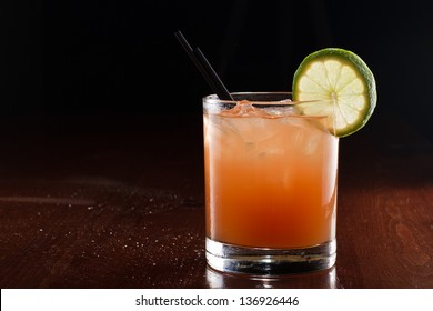 tropical juice cocktail served on a dark bar setting garnished with a lime wheel