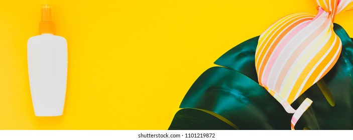 Tropical jungle palm monstera leaves, sunscreen blank bottle mockup and woman's swimsuit on bright yellow paper background. Summer vacations creative flat lay concept template text. Long wide banner