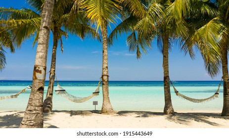 Tropical landscape: beautiful beach with hammock and tropical sea. Panglao island, Bohol, Philippines. Summer and travel vacation concept.