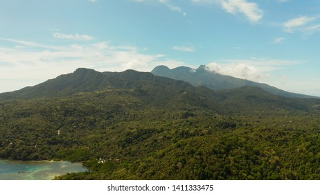Tropical landscape: Mountains with forest, against blue sea with blue sky with clouds, top view, Camiguin, Philippines. Mountain landscape on tropical island with mountain peaks covered with forest