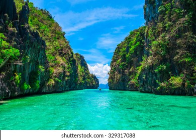 Tropical landscape with rock islands, lonely boat and crystal clear water, Palawan, Philippines