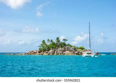 tropical landscape with yacht, palm trees, with granite rocks in the ocean