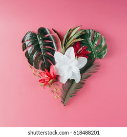 Tropical leaves and flowers in shape of a heart. Mothers day love concept. Flat lay.