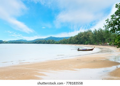 Tropical long sandy tranquil beach with blue sky and long boat at Hat Nopparat Thara beach in Ao Nang, Krabi