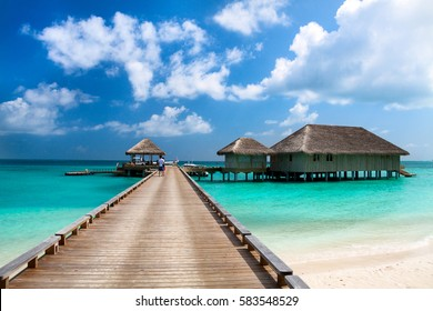 Tropical Maldives island resort on a sunny day. Luxury water villas and wooden bridge.