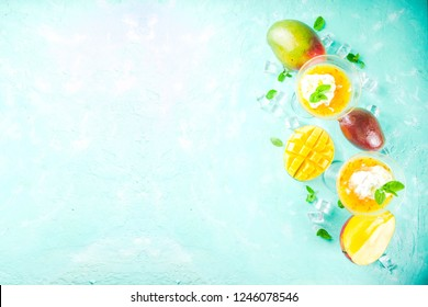 Tropical mango floating margarita cocktails with coconut ice cream, light blue background copy space