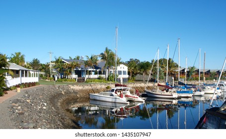 Tropical Marina waterfront foreshore landscape and moored boats in smooth harbour water with reflections under a vibrant blue sky. Tin Can Bay, Queensland, Australia.