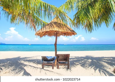 Tropical natural palm leaf umbrella and wooden beach chair on the beach under the coconut trees shading shadow overlooking the beach with blue sea at Lipe island, Satun Province, Thailand