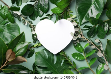 Tropical nature background with green leaves and white heart shaped paper for copy space. Top view. Flat lay. Creative advertising. Summer and love concept