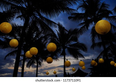 tropical night landscape at luxury beach resort with a view of palm trees under a sunset sky with lamps and lantern lights deco in Summer holidays travel destination and relax concept