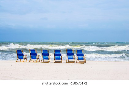 Tropical ocean beach with beach chairs on white sand shore.  Ocean waves splashing onto beach.  Scenic tourist travel destination location for relaxation and recreation.